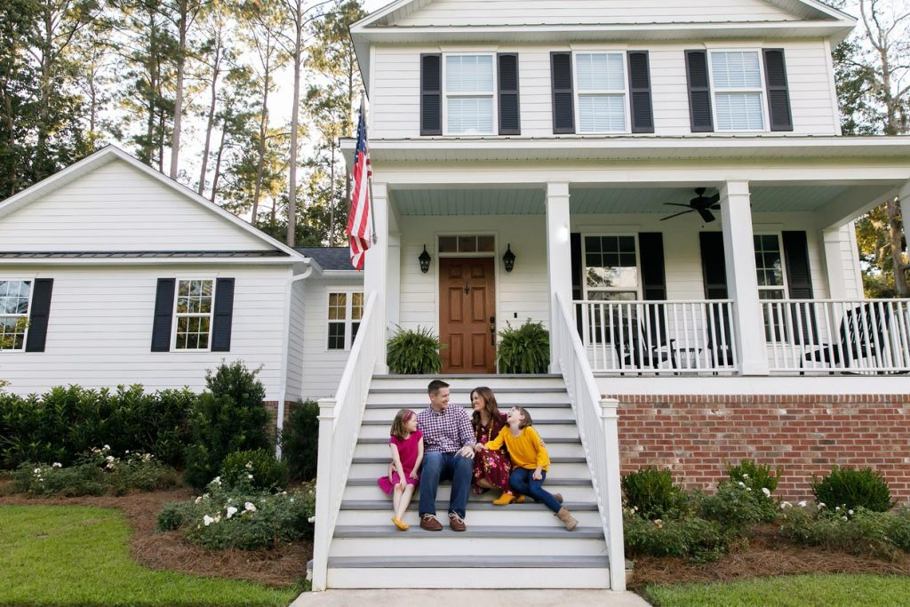 Family Sitting happily in front of Maryland home on front porch