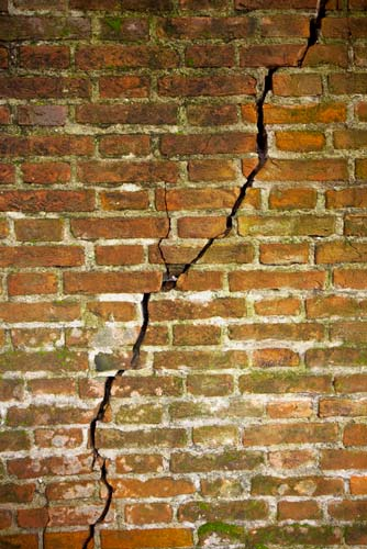 image of a crack in the foundation of a brick home